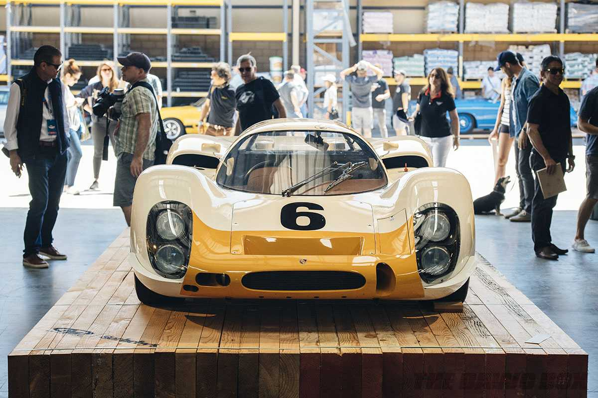 yellow and white classic porsche race car on display