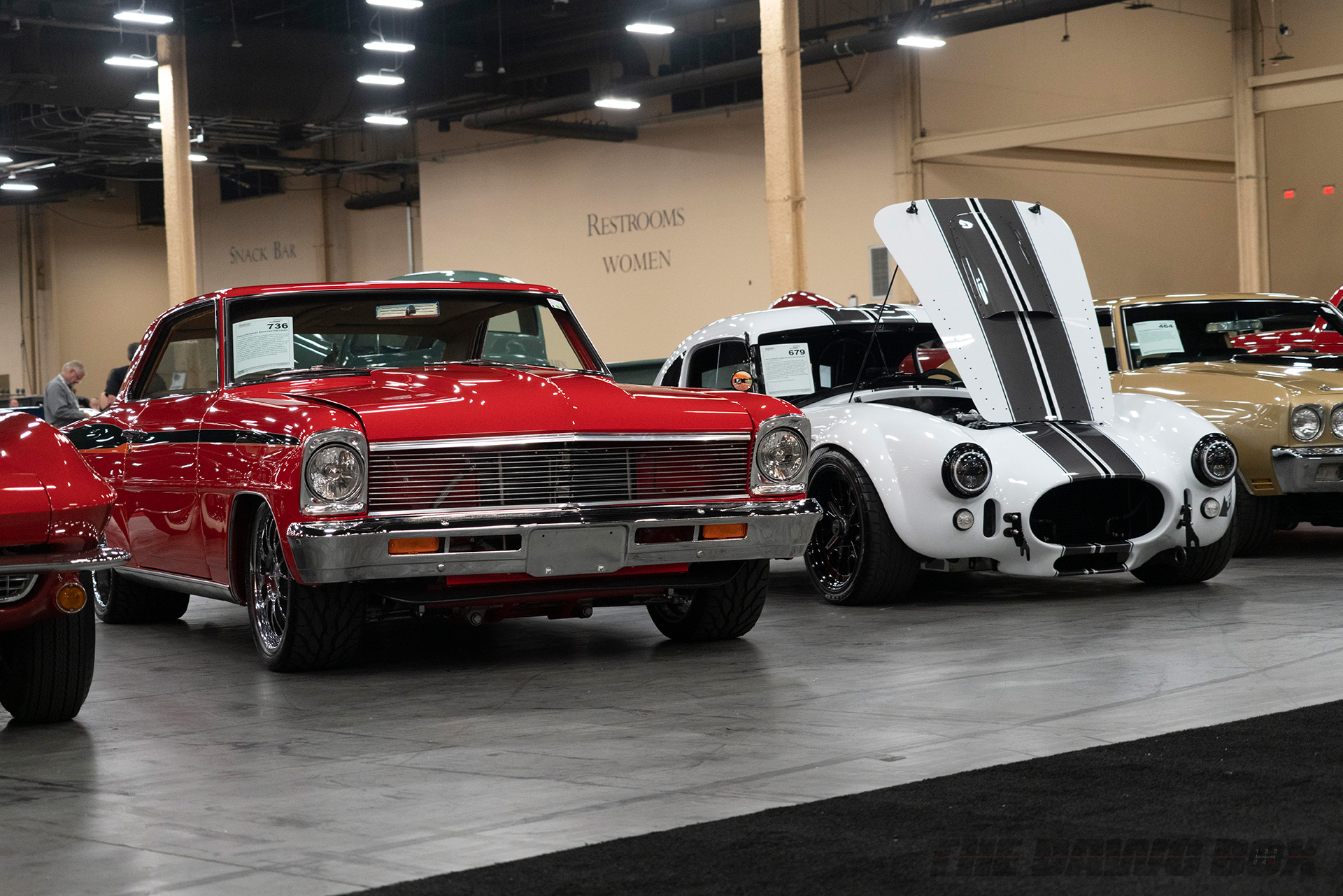 classic red muscle car and white AC cobra at Barrett-Jackson Auction