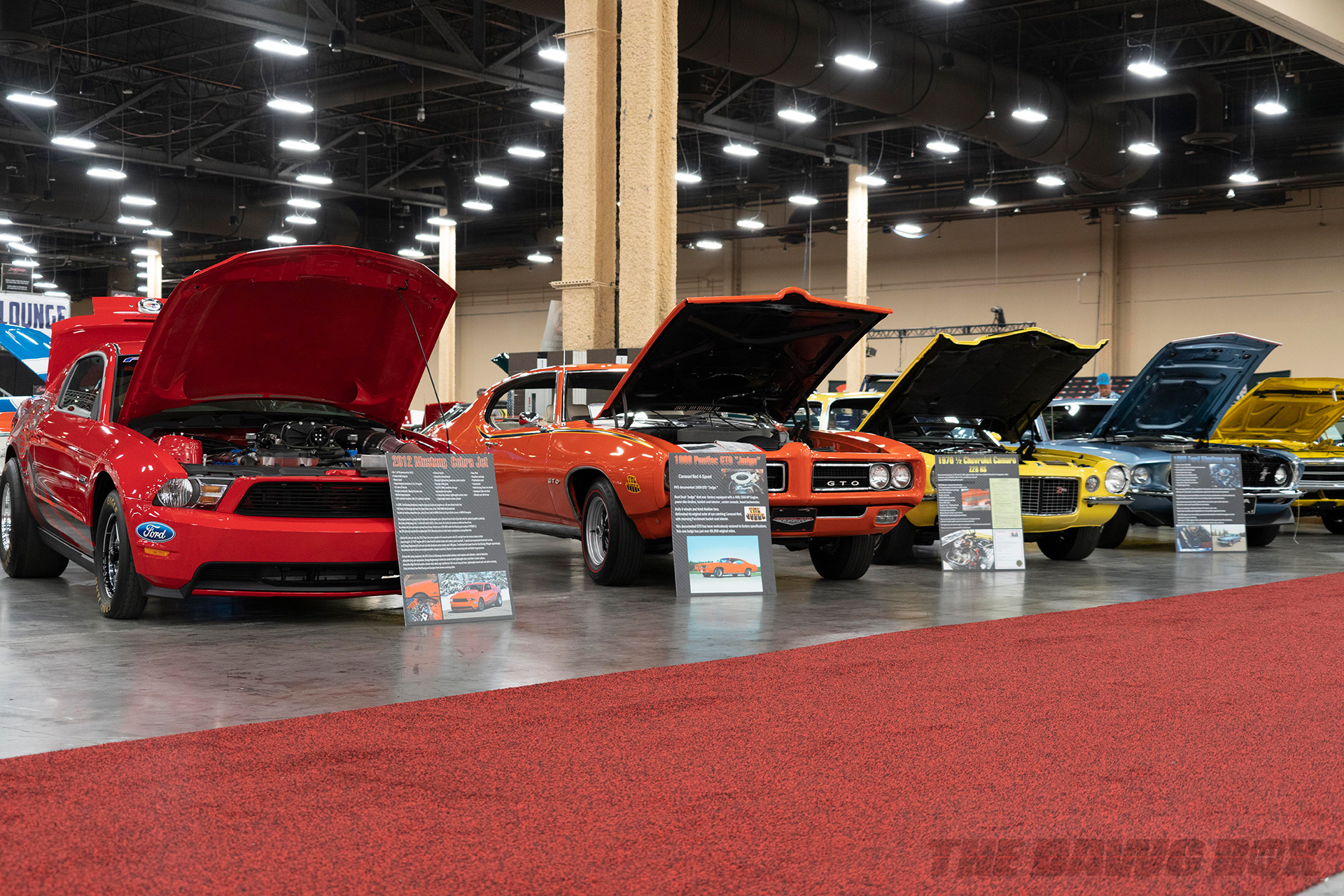 red 2012 ford mustang cobra jet, orange 1966 pontiac GTO, yellow 1970 chevy camaro z28 rs, and blue ford mustang mach 1 at Barrett-Jackson Auction