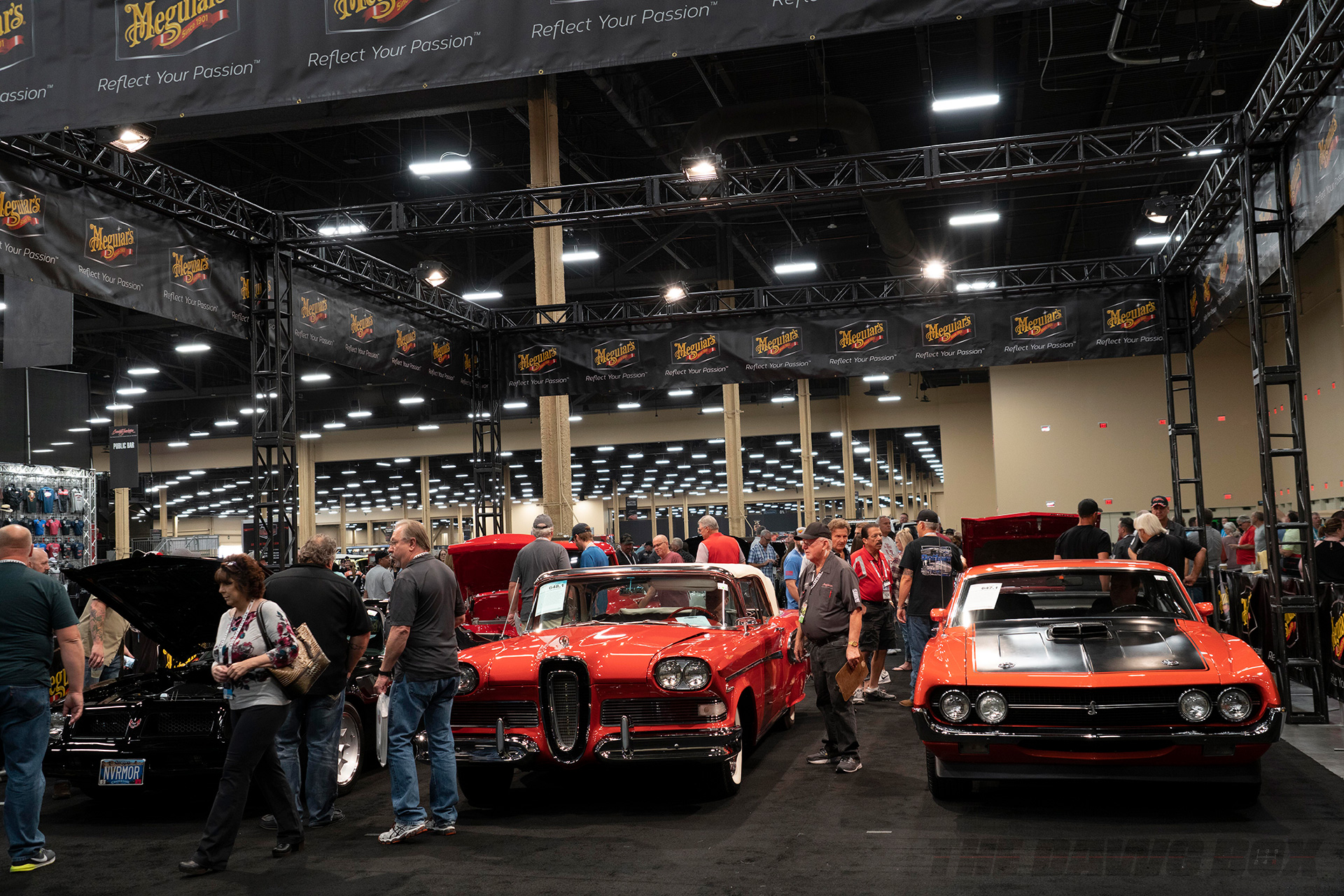 orange, red, and black classic muscle cars on display at Barrett-Jackson Auctions