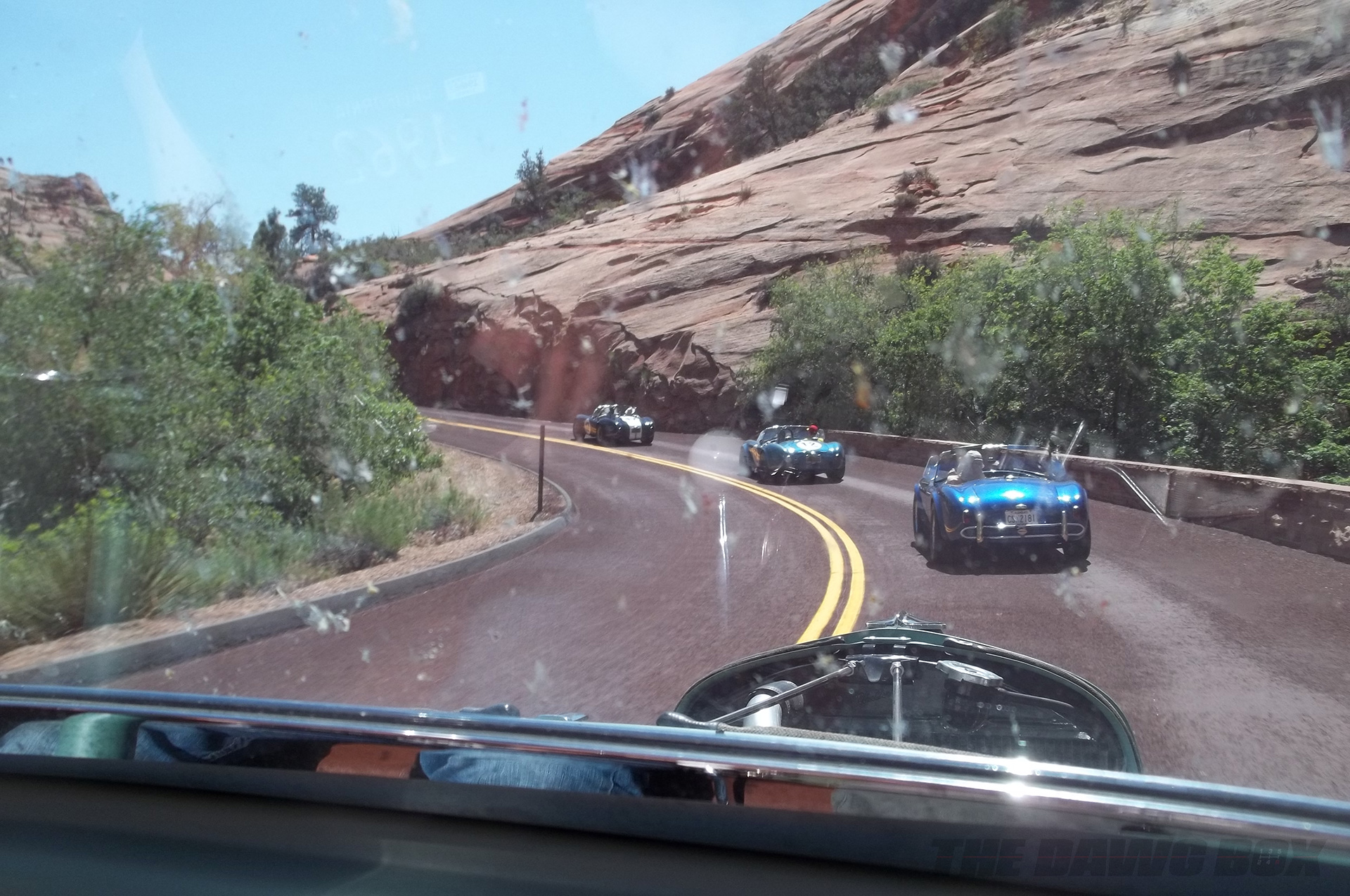 one black and 2 blue Shelby AC Cobras driving down a scenic Grand Canyon highway