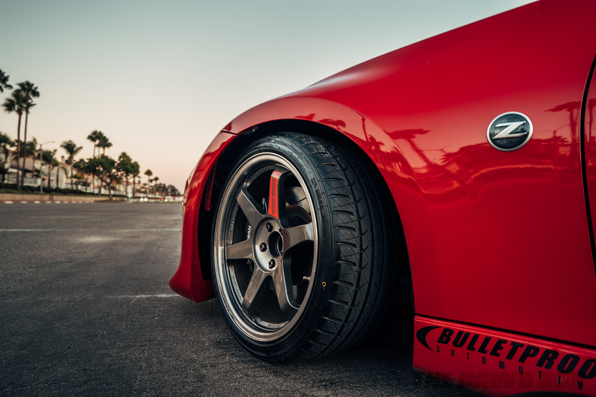 close up shot of the front driver side tire of a red Nissan 370z with Milestar Tires MS932 XP+ tires