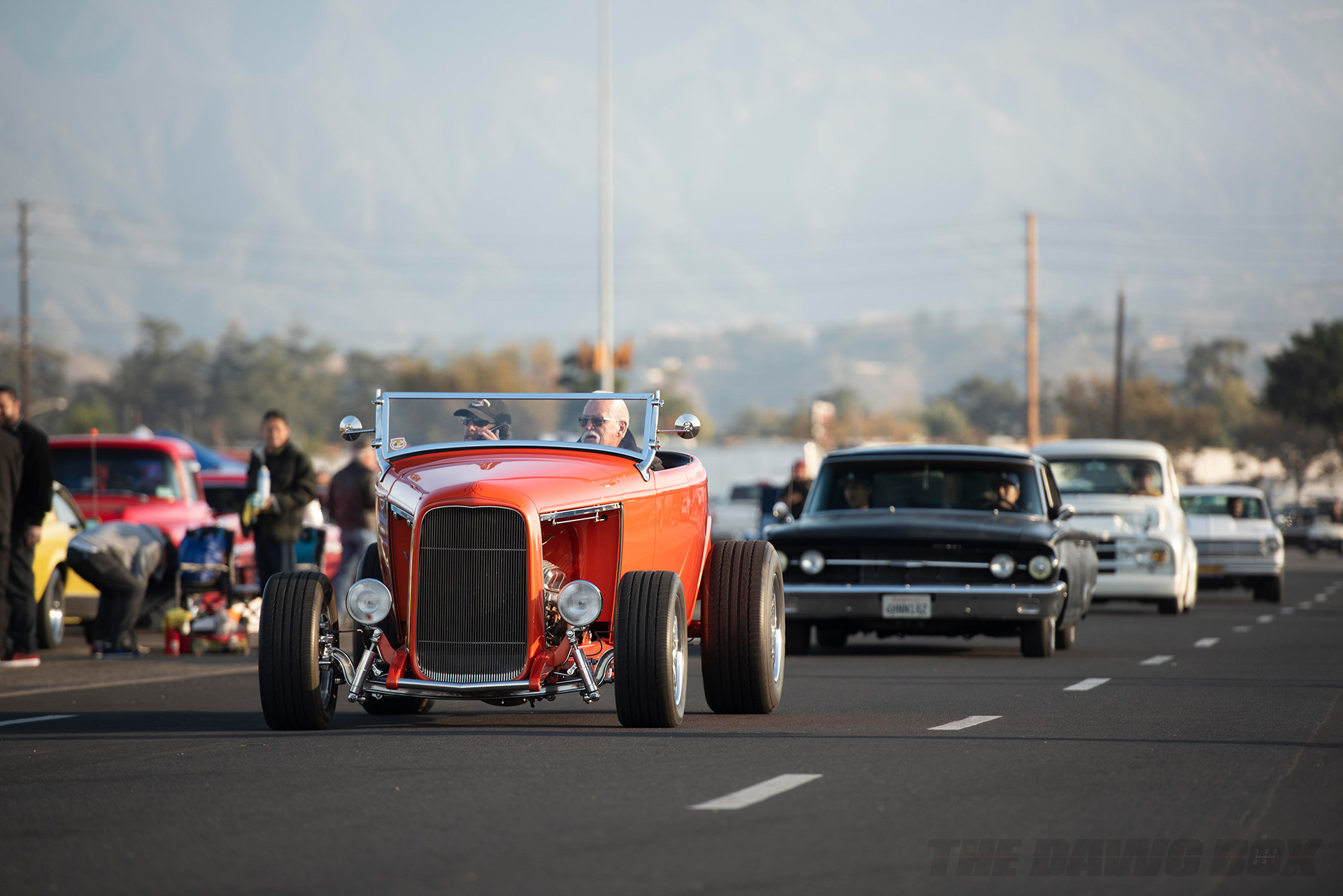 a parade of classic cars cruise down the road at the In-N-Out Hot Rod 70th Celebration