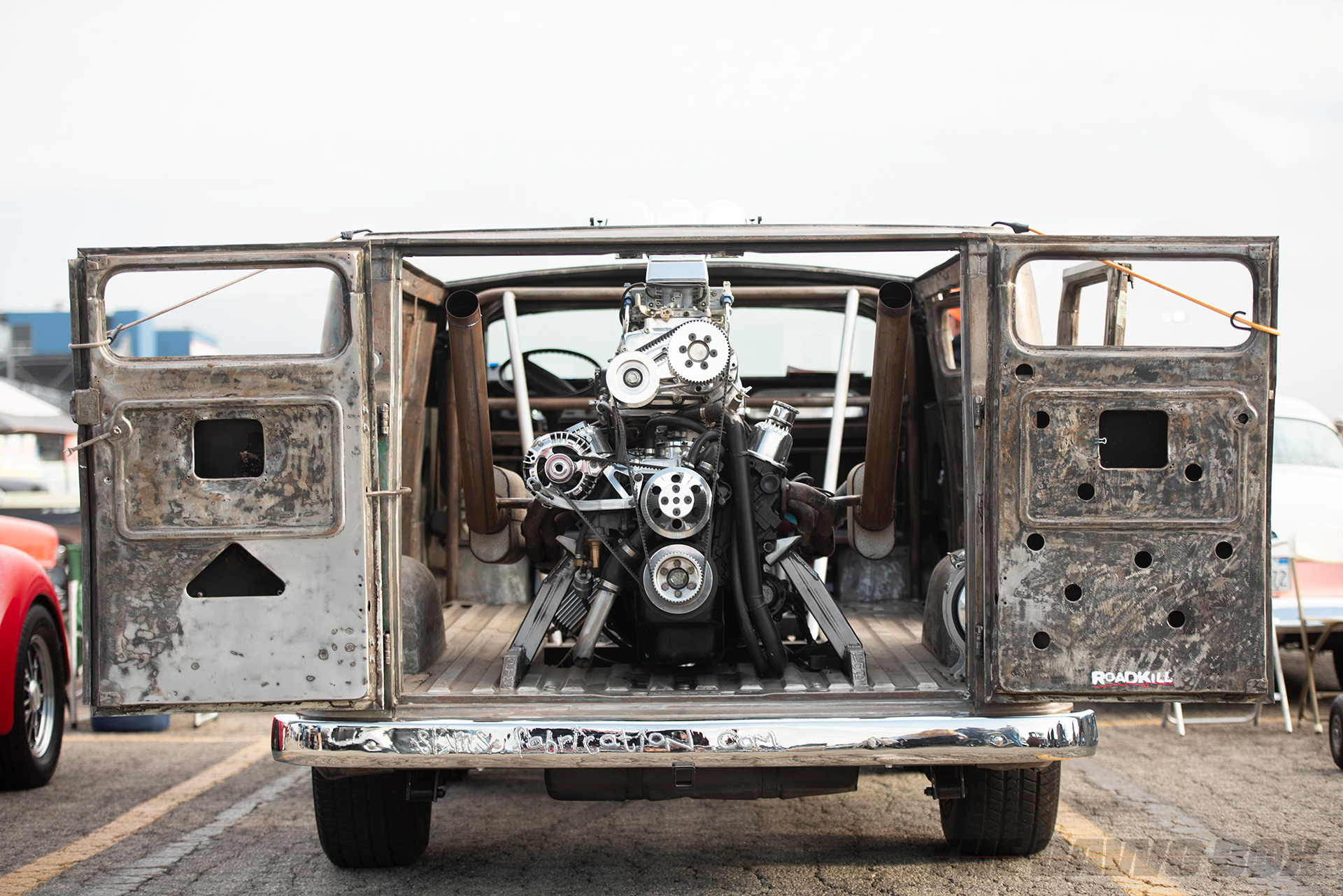 a rusted out rat rod passenger van with a rear mounted engine at the In-N-Out Hot Rod 70th Celebration