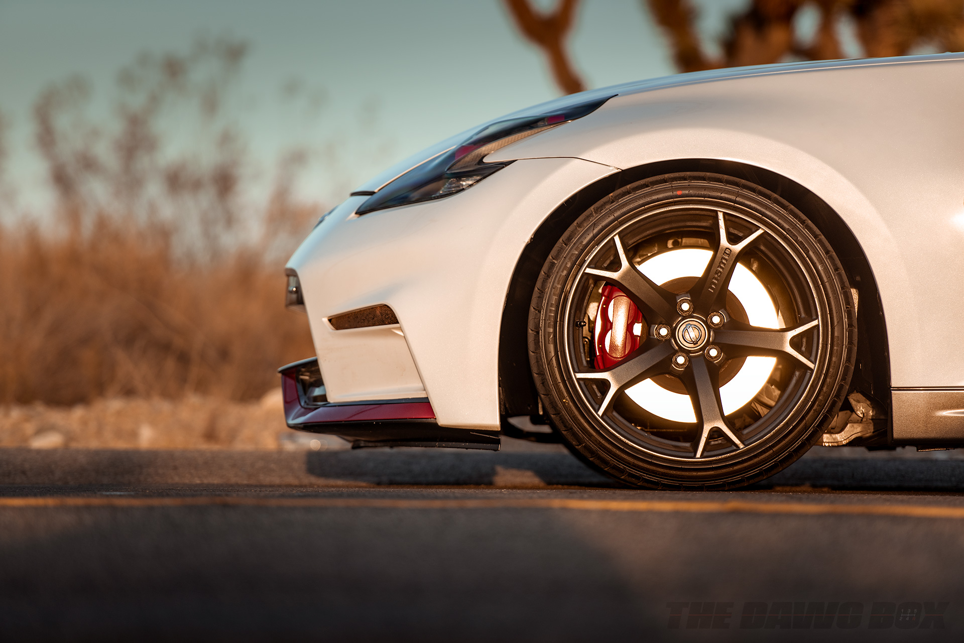 close up view of a white Nissan 370z with Milestar Tires MS932 XP+ tires on a highway in a desert