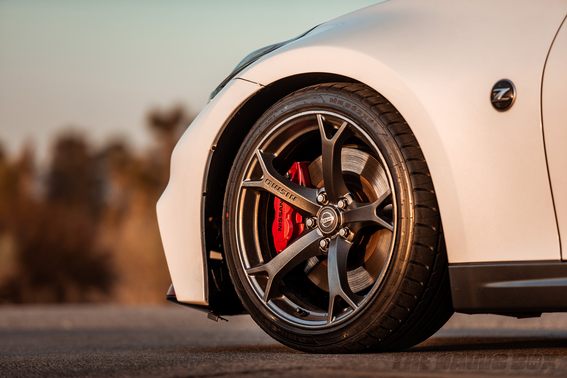 driver side wheel close up of a white Nissan 370z with Milestar Tires MS932 XP+ tires on a highway in a desert