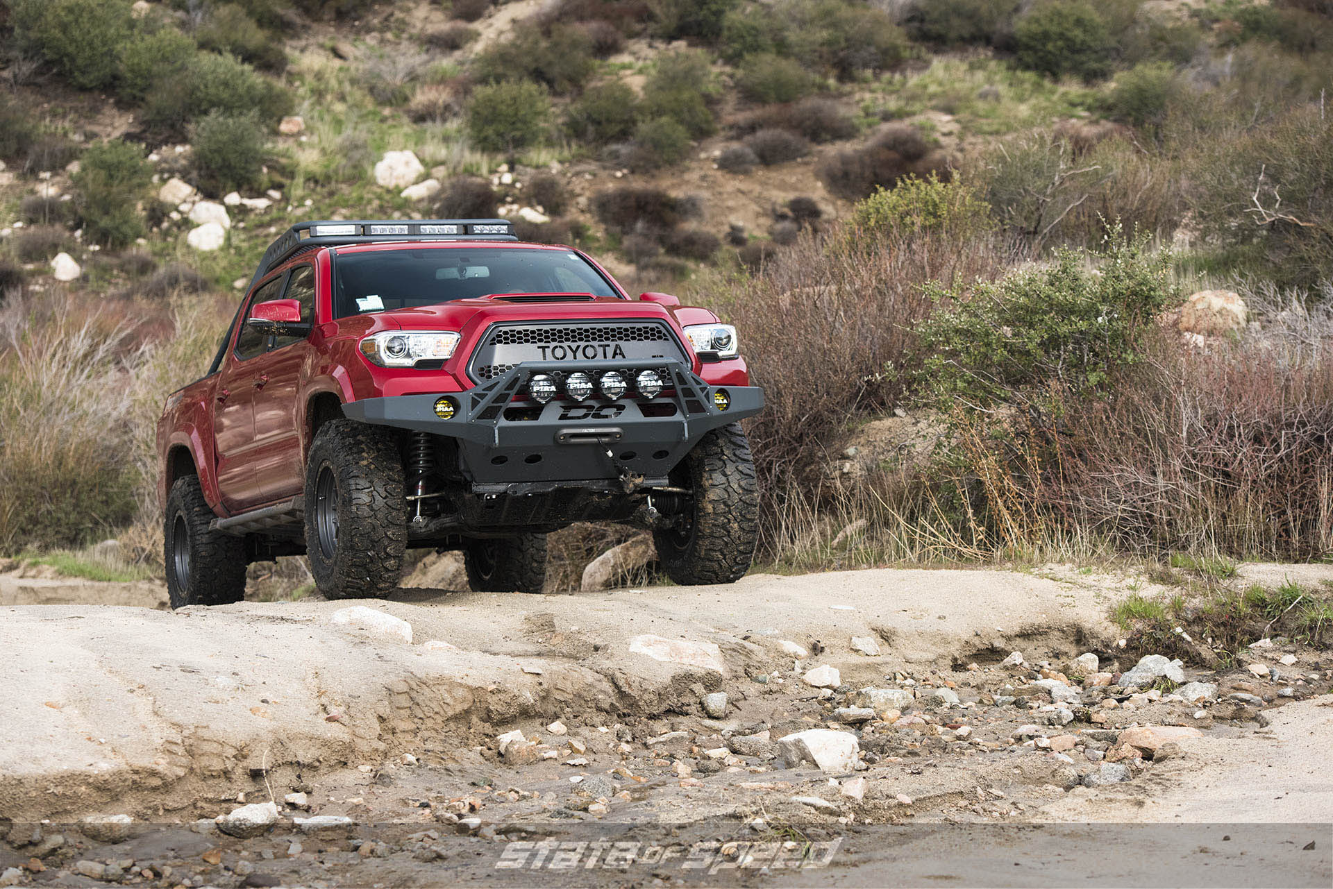 Modified Red Toyota Tacoma with Milestar Patagonia M/Ts