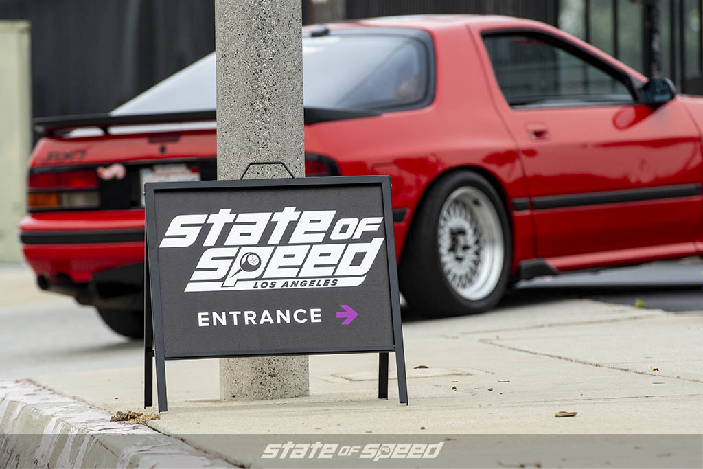 State of Speed Los Angeles LA entrance sign with red Mazda RX-7