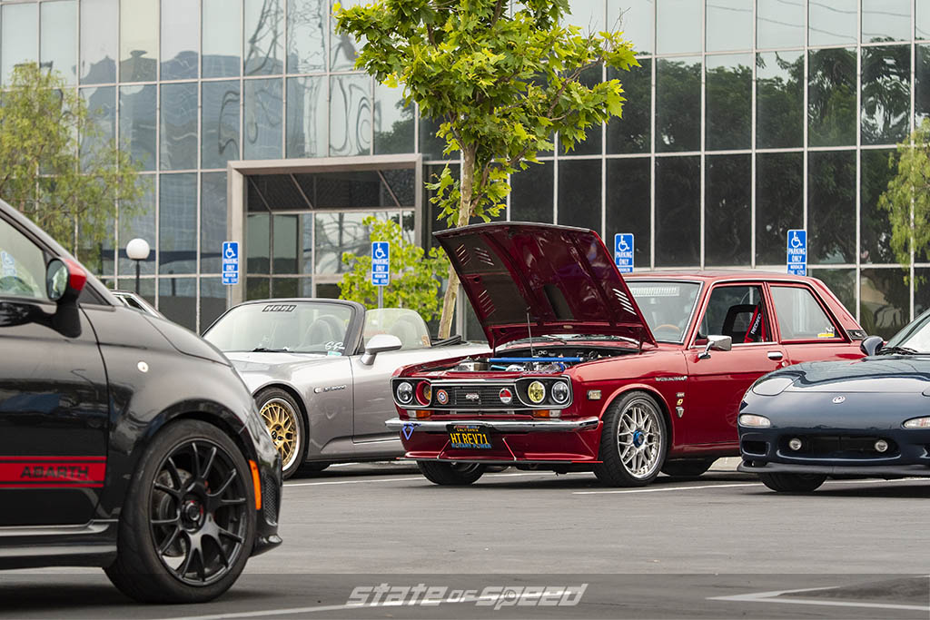 Red Datsun 1300B, dark blue Mazda RX-7,and Fiat 300 Abarth at State of Speed Los Angeles LA