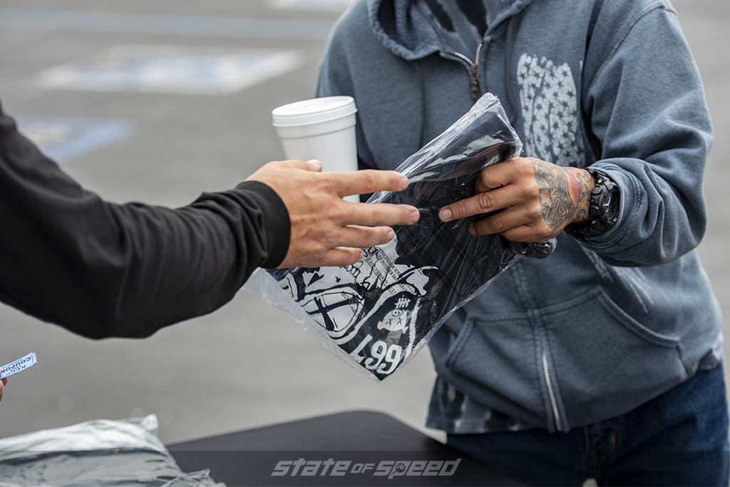 Man giving a visitor a free State of Speed T-shirt at State of Speed Los Angeles LA car meet