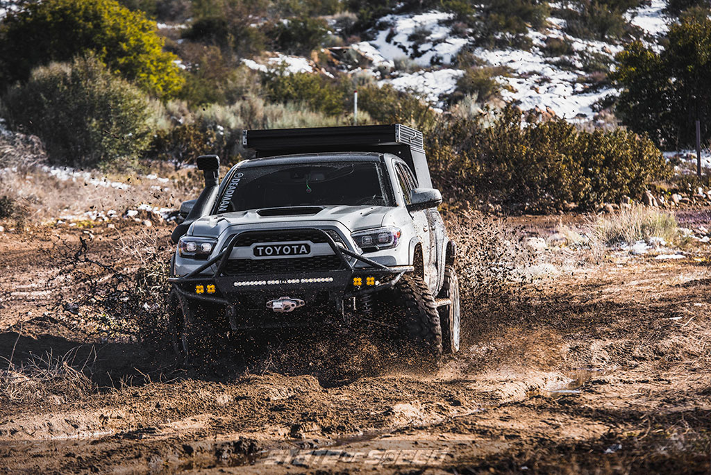 """Toyota Tacoma with 35"""" tires offroad running through the mud"""