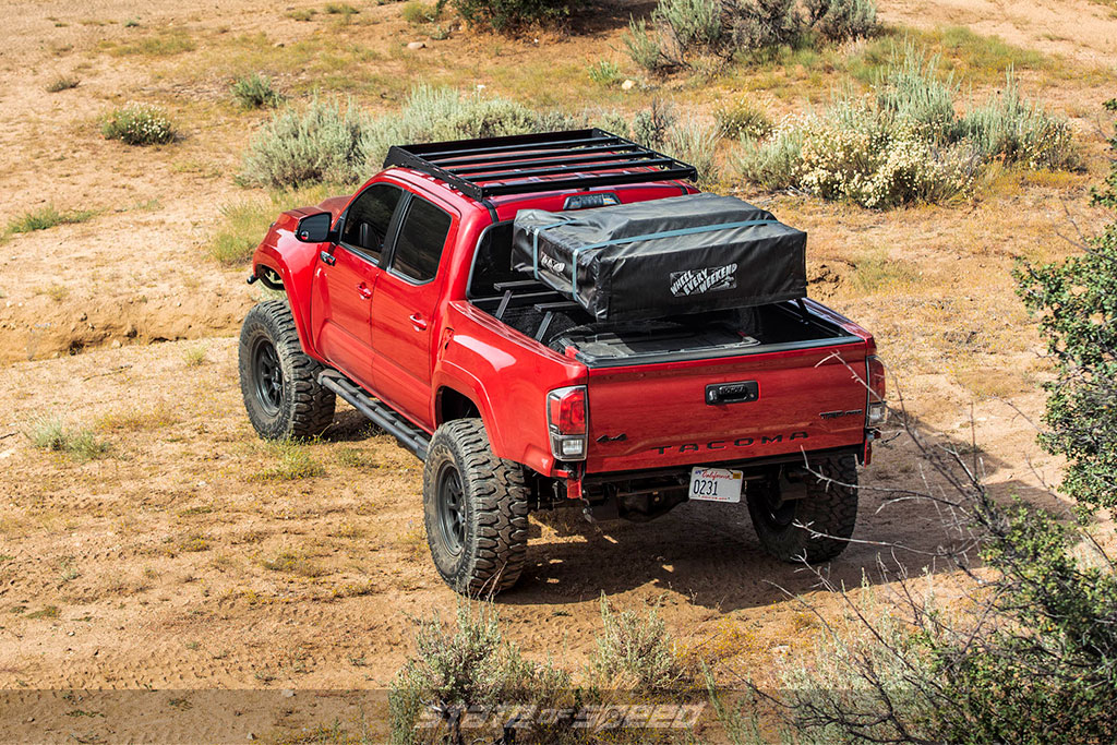 Red overland toyota tacoma with Patagonia MT offroad tires
