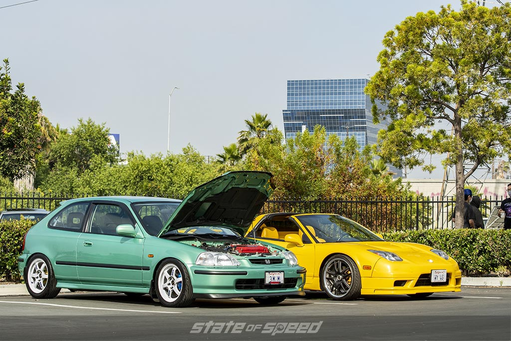 green honda civic hatchback with its hood open showing a modified b-series engine parked next to a yellow honda/acura NSX