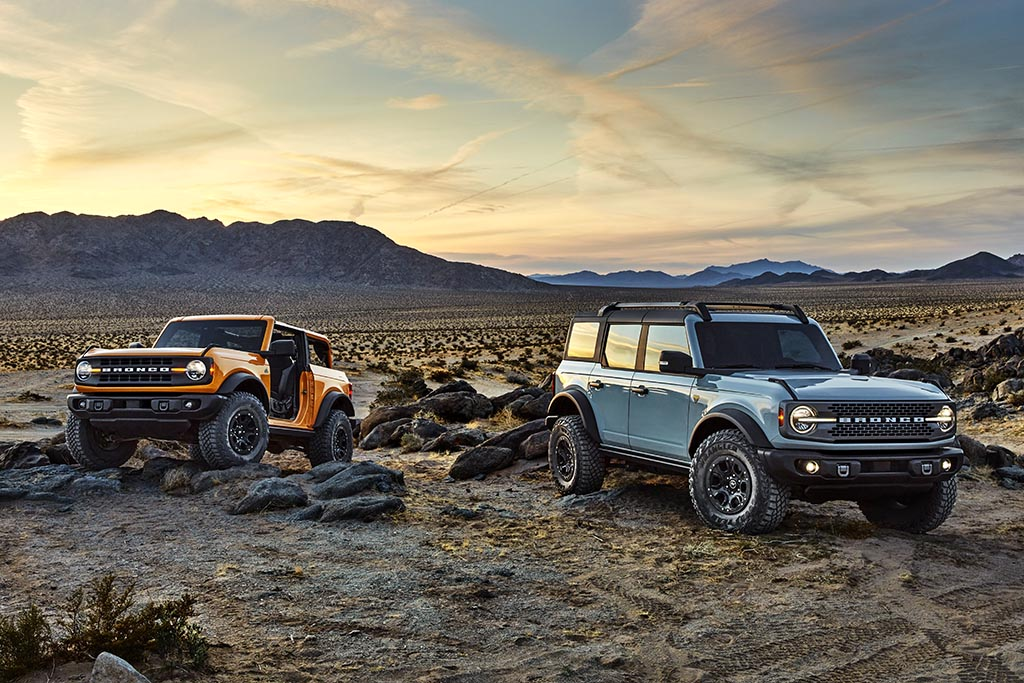 Pre-production versions of the 2021 Bronco, shown here, include Bronco two-door in Cyber Orange Metallic Tri-Coat and Bronco four-door in Cactus Gray in a mountainous desert during sunset
