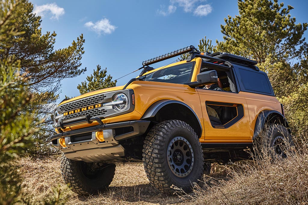 Yellow 2021 Ford Bronco with modular windowed doors trekking through a forest on a sunny day
