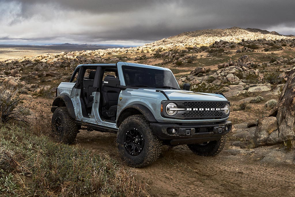 Pre-production 2021 Bronco four-door Badlands series with available Sasquatch™ off-road package in Cactus Gray with the doors, top and rear quarter windows removed in a rocky desert during a cloudy day