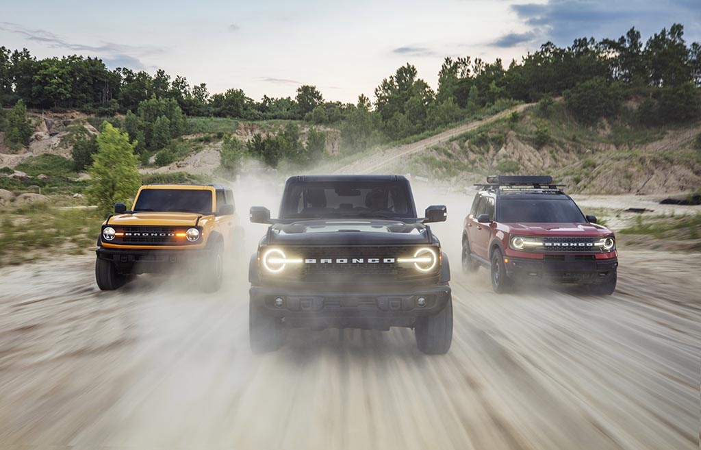 Pre-production versions of the all-new 2021 Bronco family of all-4x4 rugged SUVs, shown here, include (left) Bronco two-door in Cyber Orange Metallic Tri-Coat, Bronco four-door in Shadow Black and Bronco Sport in Rapid Red Metallic Tinted Clearcoat, all speeding through a forest dirt road.