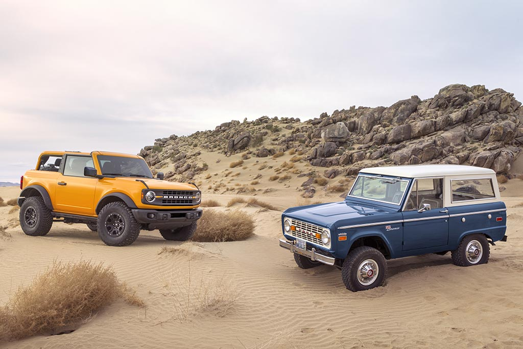 Pre-production 2021 Bronco two-door SUV takes its rugged off-road design cues from the first-generation Bronco, the iconic 4x4 that inspired generations of fans. yellow 2021 ford bronco next to a blue first generation ford bronco in a sandy desert