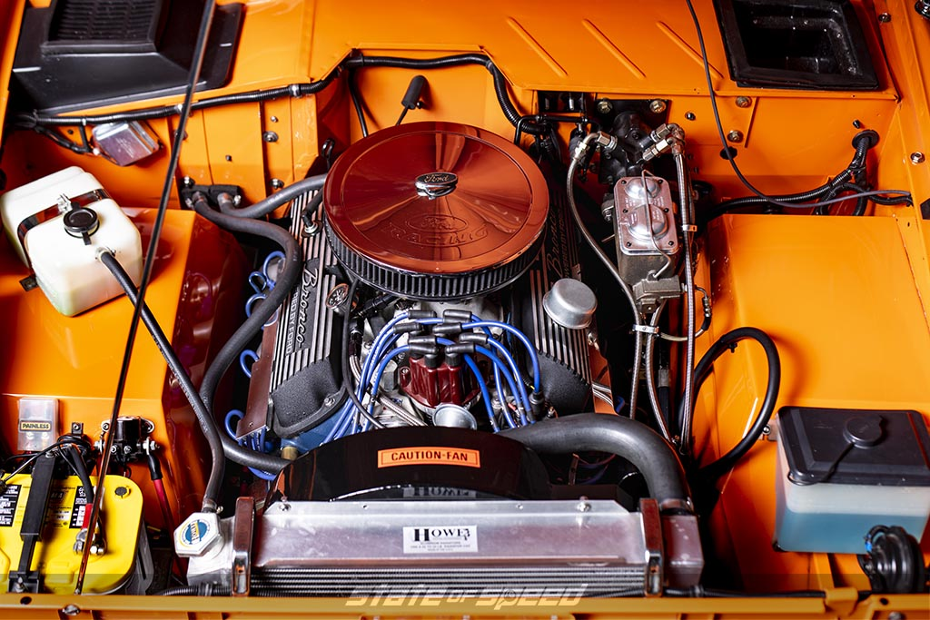 Classic first generation ford bronco engine in an orange ford bronco