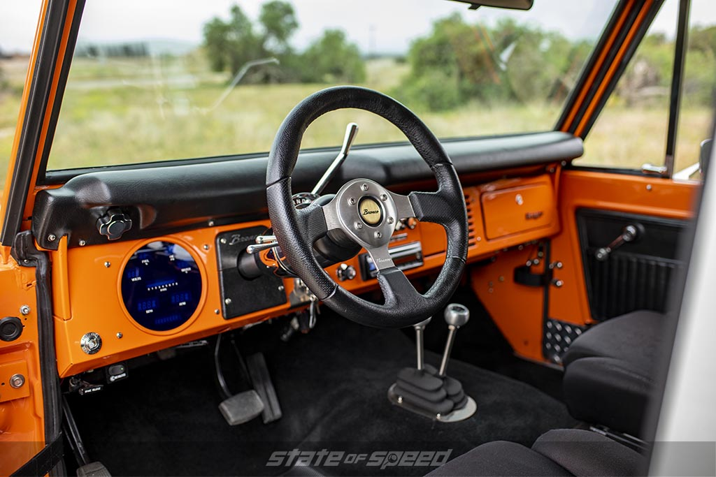 Slightly modernized first generation '76 Ford Bronco Interior in orange with a digital gauge cluster in place of the original speedometer