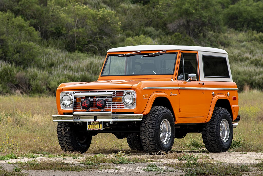 Orange first generation ford bronco on milestar patagonia M/T Tires in a green mountainous area