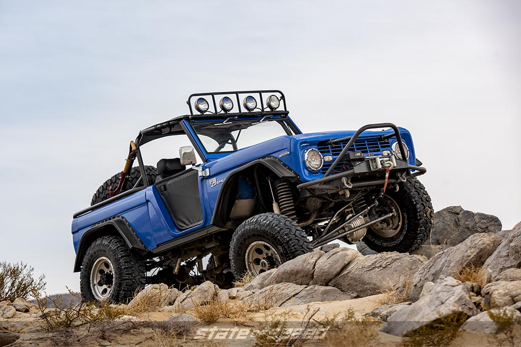 custom Blue first generation 1966 Ford Bronco crawling over some rocks in a desert