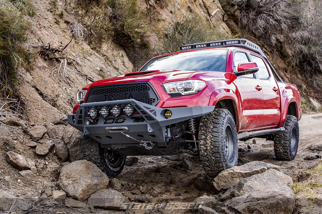 Red Toyota Tacoma Crawling over some rocks