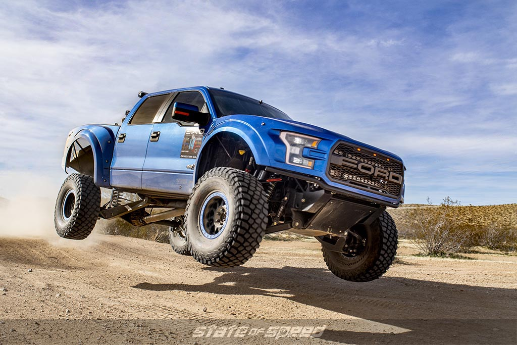 Blue Ford F-150 Raptor Gen 2 modified by SVC jumping over a hill